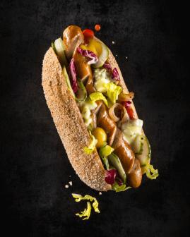Holy Dogs Premium Hot Dog mit Bio-Wiener, Mischsalat, Schmorzwiebeln, Gurkenscheiben, Holy-Soße