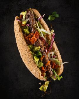 Holy Dogs Premium Hot Dog mit Bio-Beef-Roll, Mischsalat, Avocado-Creme, fruchtig-feurige Tomaten-Salsa, Chilifäden