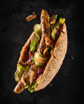 Holy Dogs Premium Hot Dog mit Bio-Bratwurst, Mischsalat, BBQ-Soße, Schmorzwiebeln, Gurkenscheiben, Specksplitter